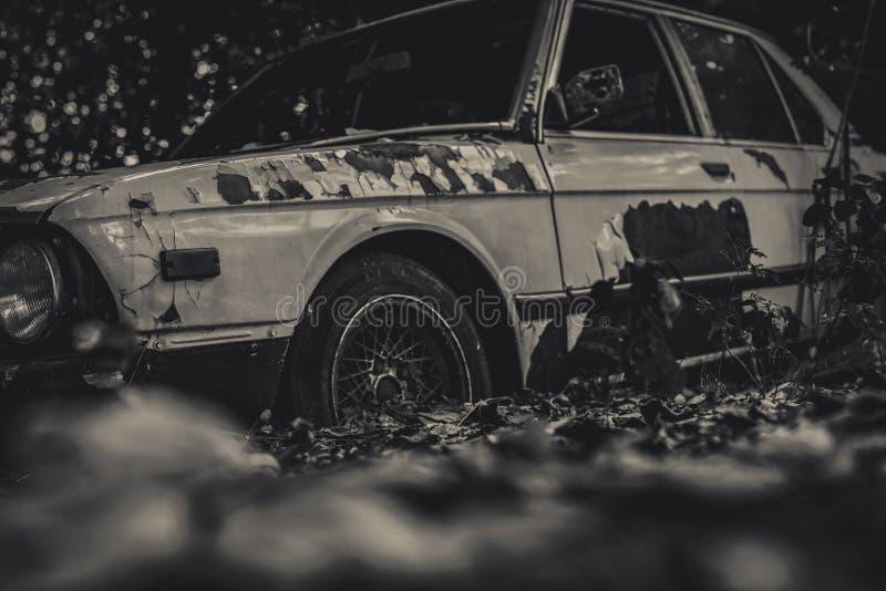 Coche arruinado viejo en escena blanco y negro Coche oxidado abandonado en el bosque en fondo del bokeh Abandono arruinado decaíd fotos de archivo libres de regalías