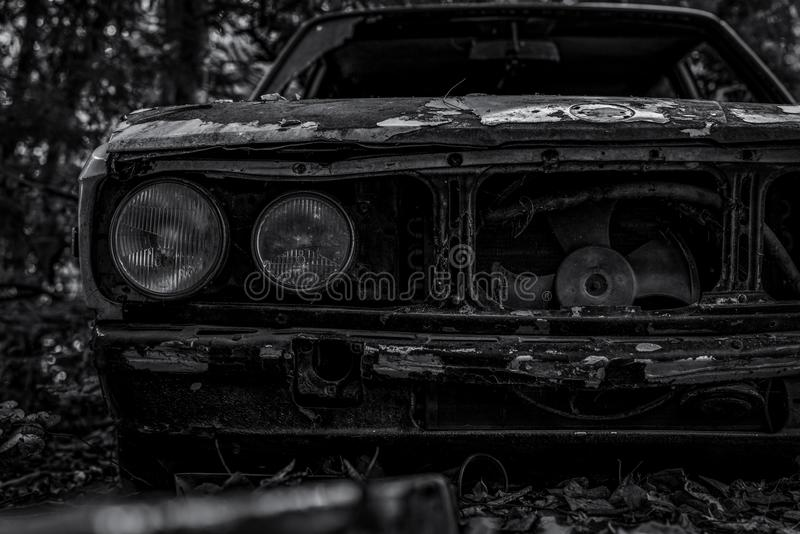 Coche arruinado viejo en escena blanco y negro Coche oxidado abandonado en la vista delantera del primer del bosque del coche arr fotografía de archivo libre de regalías