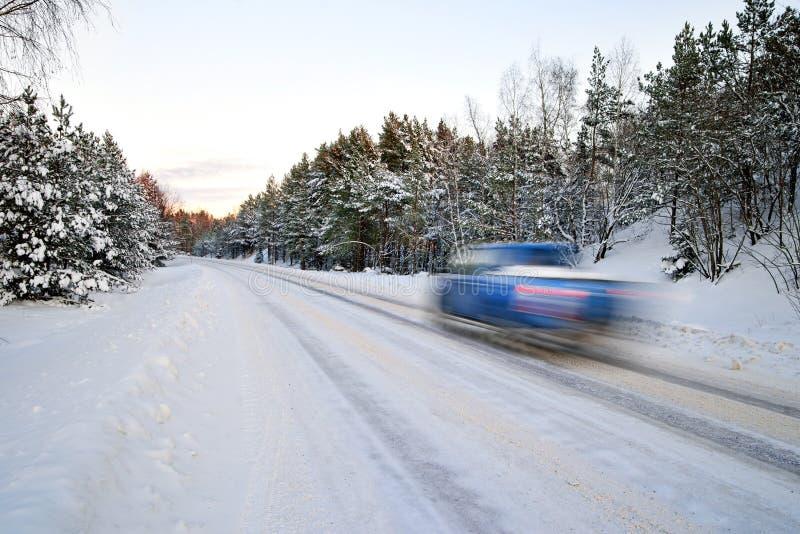 Coche azul en el camino del invierno fotos de archivo