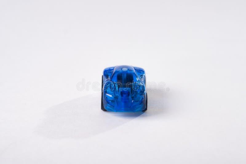 Coche azul plástico del juguete en el fondo blanco, diseño simple, el juguete de los niños foto de archivo