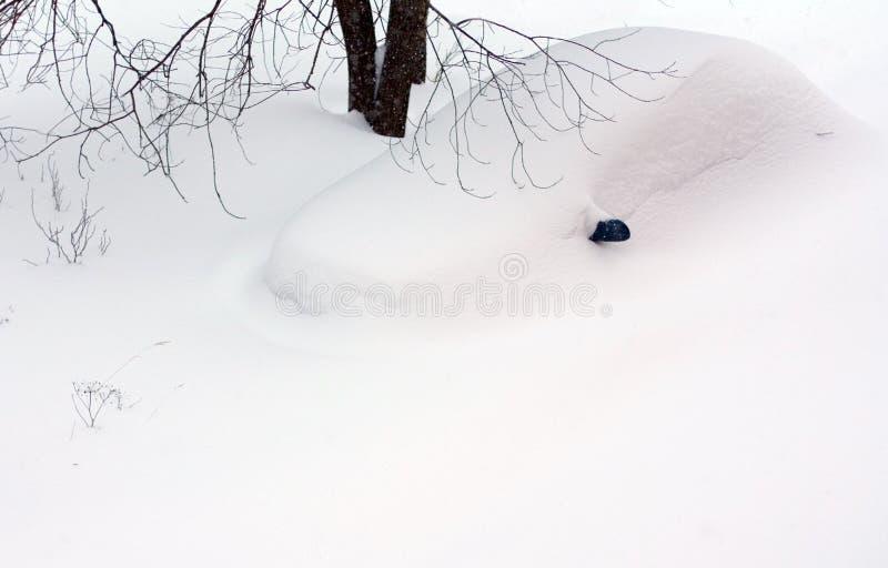 Coche bajo la nieve acumulada por la ventisca fotos de archivo