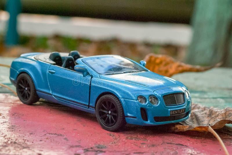 Coche Bentley Continental modelo 2010 del juguete Color azul Vista lateral En las hojas de hojas caidas Primer fotos de archivo libres de regalías