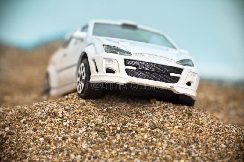Coche blanco del juguete que compite con en terreno áspero imagen de archivo