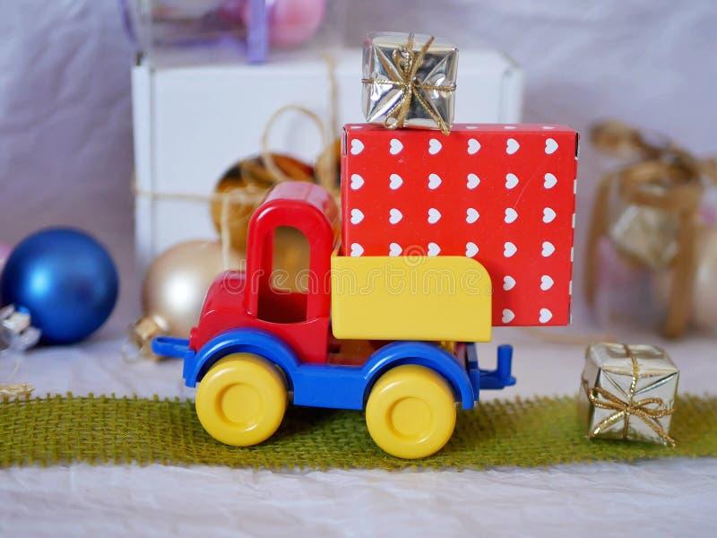 Coche brillante del juguete, cajas con los regalos, decoraciones de la Navidad, la decoración del Año Nuevo, bolas en un fondo li foto de archivo