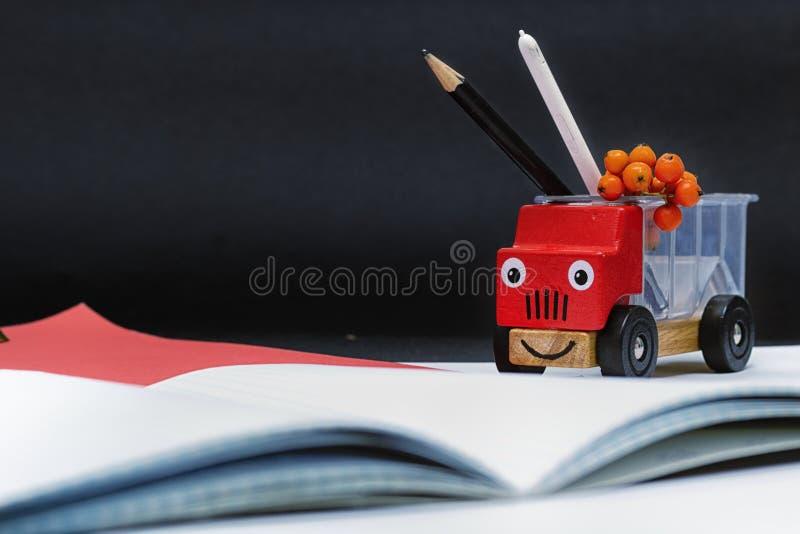 Coche camión del juguete en la derecha en un fondo negro En la parte posterior de las fuentes de escuela dibuje a lápiz y aguja S fotos de archivo