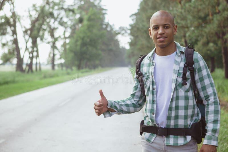 Coche cathing del hombre africano hermoso en el camino mientras que hace autostop foto de archivo