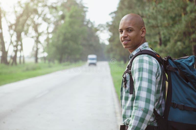 Coche cathing del hombre africano hermoso en el camino mientras que hace autostop imágenes de archivo libres de regalías