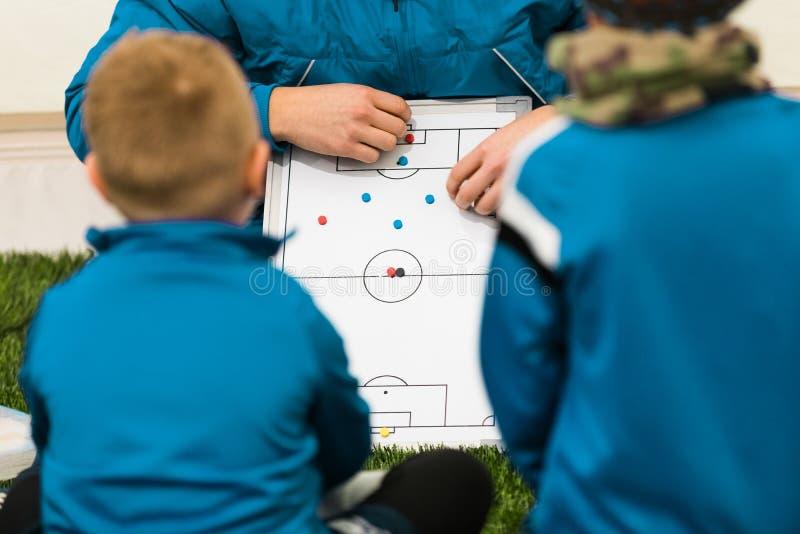 Coche Coaching Children del fútbol de la juventud Táctica de los coches de los jugadores de fútbol de los muchachos que escuchan  fotografía de archivo libre de regalías