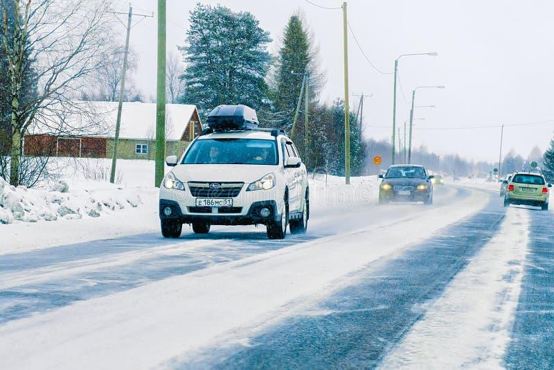 Coche con el estante de equipaje del tejado en el invierno Rovaniemi Finlandia del camino imagen de archivo libre de regalías