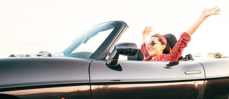 Coche convertible de conducción femenino sonriente alegre joven en el sitio web de los jefes del tiempo del día soleado fotografía de archivo libre de regalías
