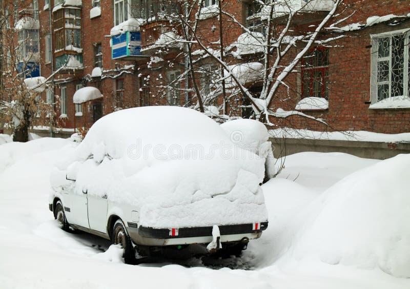 Coche cubierto por una nieve acumulada por la ventisca fotografía de archivo libre de regalías
