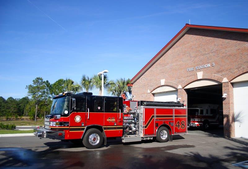 Coche de bomberos estacionado delante de la estación número 3 imagenes de archivo