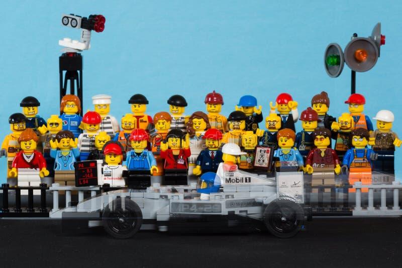 Coche de carreras del formule 1 de Lego que se mueve delante de la audiencia imagen de archivo libre de regalías