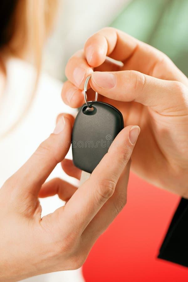 Coche de compra de la mujer - clave que es dado imagen de archivo