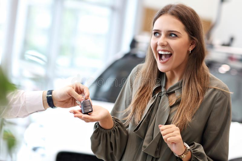 Coche de compra feliz de la mujer joven en la sala de exposición foto de archivo