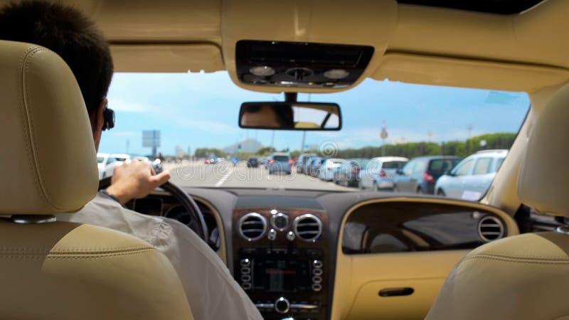 Coche de conducción masculino rico ocupado en la ciudad de vacaciones, hombre de negocios que va al encuentro, lujo imágenes de archivo libres de regalías