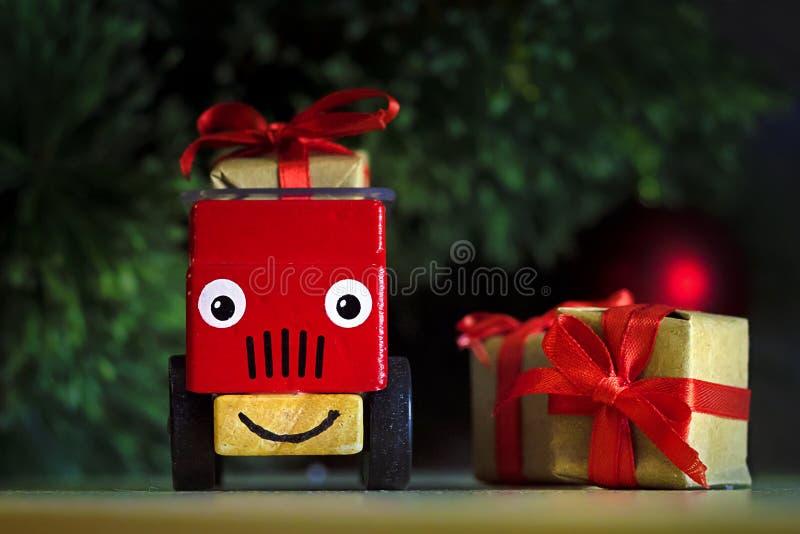 Coche de juguete para niños rojos con cajas de regalo con un arco rojo debajo del árbol de Navidad imagen de archivo