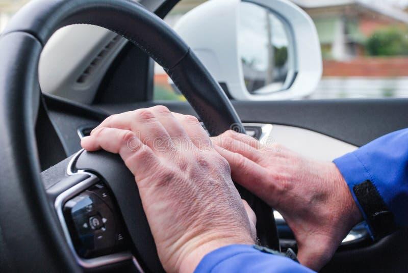 Coche de la conducción a la derecha, mano en el bocinazo de la rueda, driver& x27; las manos en el tiro, control de s de travesía imagen de archivo