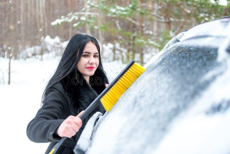 Coche de la limpieza de la mujer de la nieve con el cepillo Transporte, invierno, fotografía de archivo libre de regalías