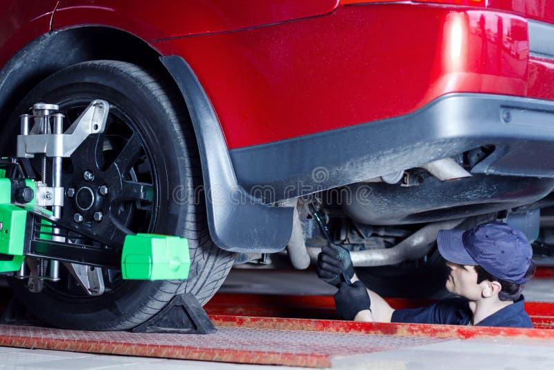 Coche de la reparación del ingeniero del mecánico en la gasolinera del coche foto de archivo
