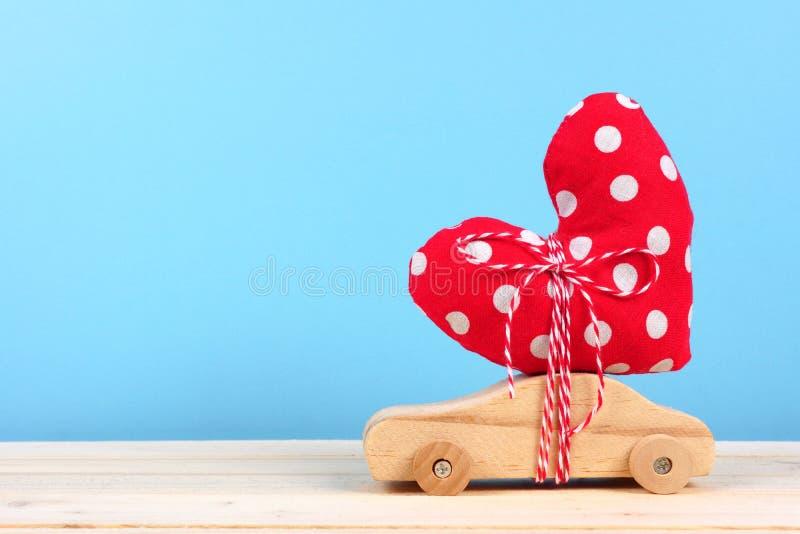 Coche de madera con el corazón del paño contra azul fotografía de archivo