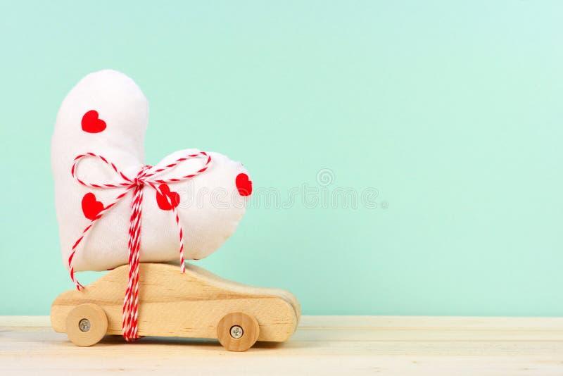 Coche de madera con el corazón del paño contra fondo de la turquesa imagen de archivo