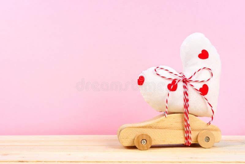 Coche de madera con el corazón del paño contra rosa foto de archivo