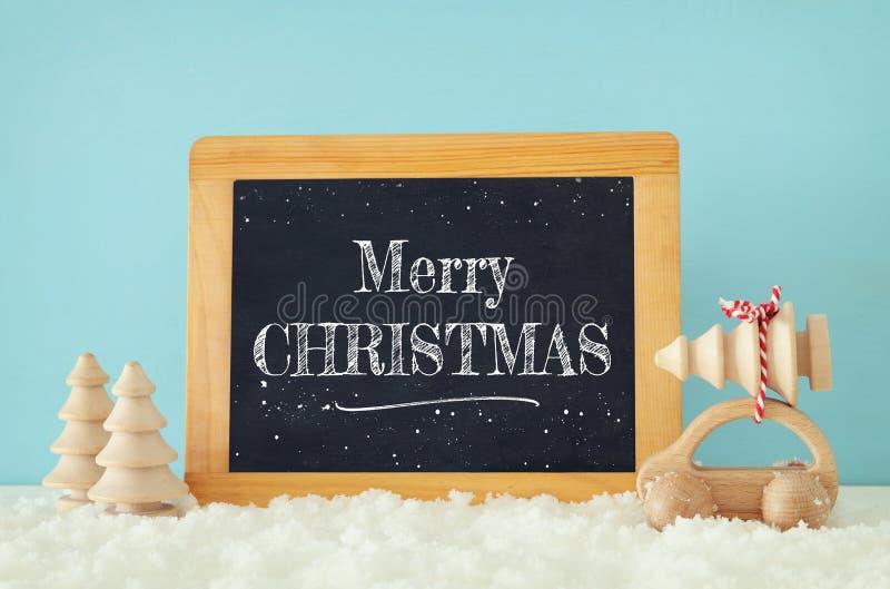 Coche de madera que lleva un árbol de navidad al lado de la pizarra delante del fondo azul fotografía de archivo libre de regalías