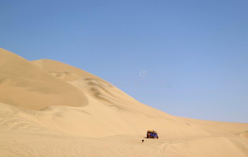 Coche de playa de funcionamiento que persigue por un perro travieso en las dunas de arena del desierto de Huacachina, región del  fotos de archivo libres de regalías