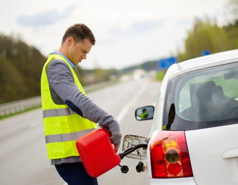 Coche de reaprovisionamiento de combustible del hombre en un borde de la carretera foto de archivo