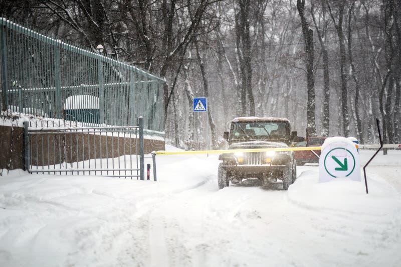 Coche de SUV parado en la puerta automática de la entrada durante las nevadas pesadas Sistema de la entrada del acceso del vehícu imagen de archivo libre de regalías