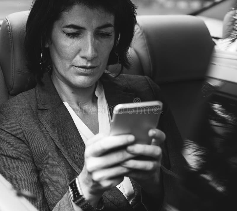 Coche de Using Smart Phone de la empresaria dentro imágenes de archivo libres de regalías