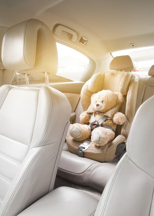 Coche del asiento del ni?o del beb? Un oso de peluche beige se sujeta con los cinturones de seguridad en un asiento de carro Reco imágenes de archivo libres de regalías