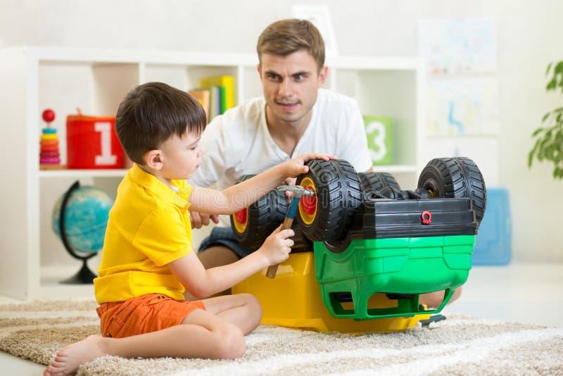 Coche del juguete de la reparación del muchacho y del padre del niño fotos de archivo libres de regalías