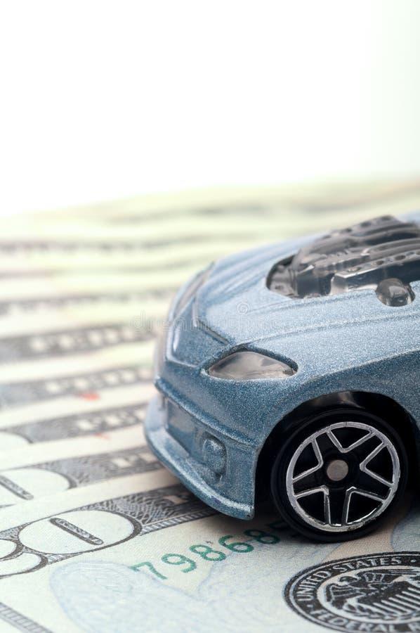Coche del juguete que se sienta en el dinero en circulación: nuevo préstamo de coche imágenes de archivo libres de regalías