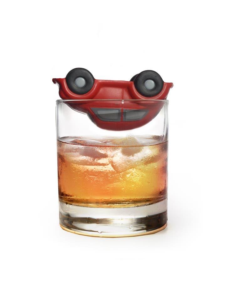 Coche del juguete sobre el vidrio de whisky como accidente de tráfico debido al alcohol imagenes de archivo