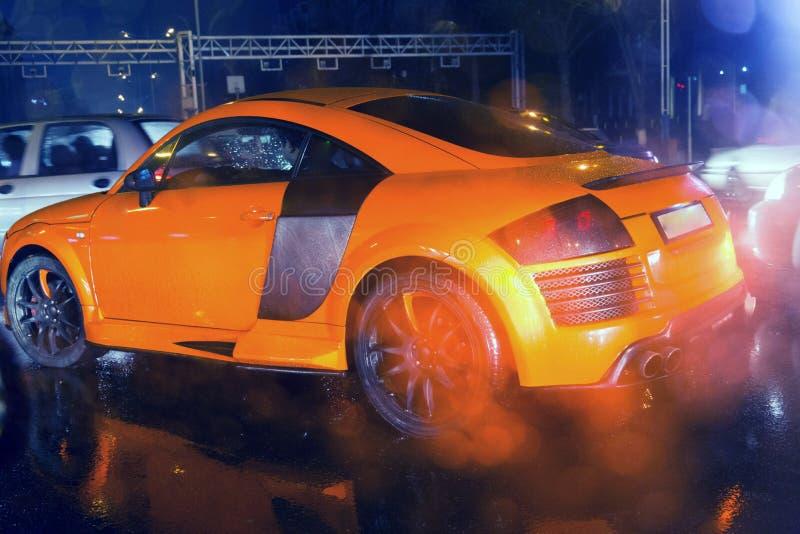 Coche deportivo anaranjado agresivo y brutal en la imagen llovida del camino útil para el fondo imagen de archivo
