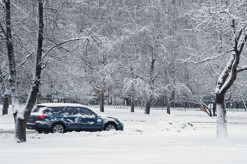 Coche durante nevadas en ciudad imagenes de archivo