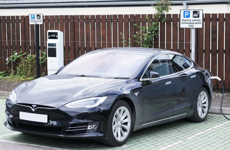 Coche eléctrico de Tesla que carga en zona de estacionamiento fotografía de archivo