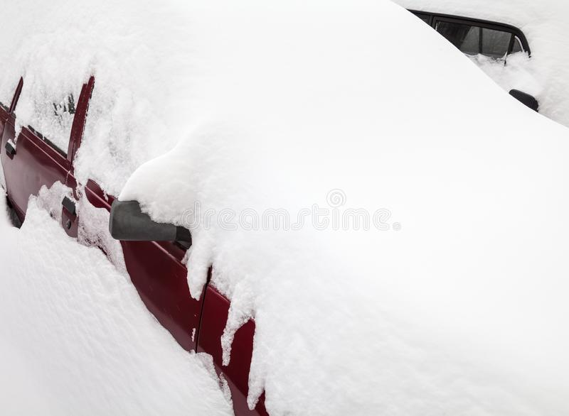 Coche en la nieve acumulada por la ventisca en el estacionamiento fotografía de archivo