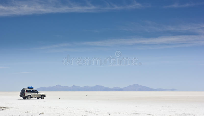 Coche en Salar de Uyuni en la superficie blanca imagen de archivo libre de regalías