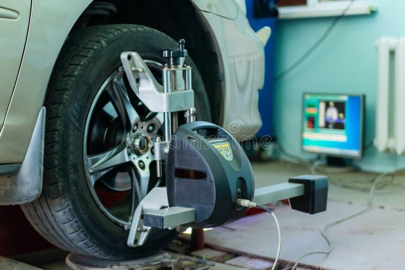 Coche en soporte con los sensores en las ruedas para el taller del incorporar de la comba de la alineación de ruedas de la gasoli imagen de archivo libre de regalías