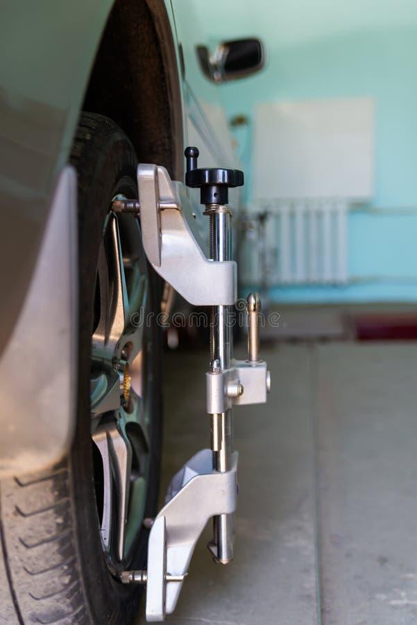 Coche en soporte con los sensores en las ruedas para el taller del incorporar de la comba de la alineación de ruedas de la gasoli fotografía de archivo