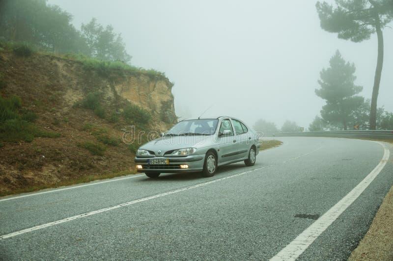 Coche en un camino que pasa con paisaje de madera con la niebla fotografía de archivo libre de regalías