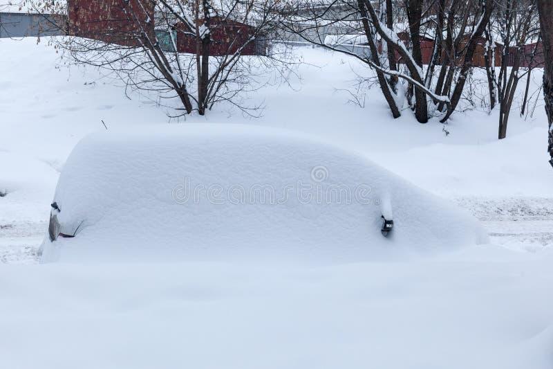 Coche en una nieve acumulada por la ventisca después de nevadas fuertes fotos de archivo