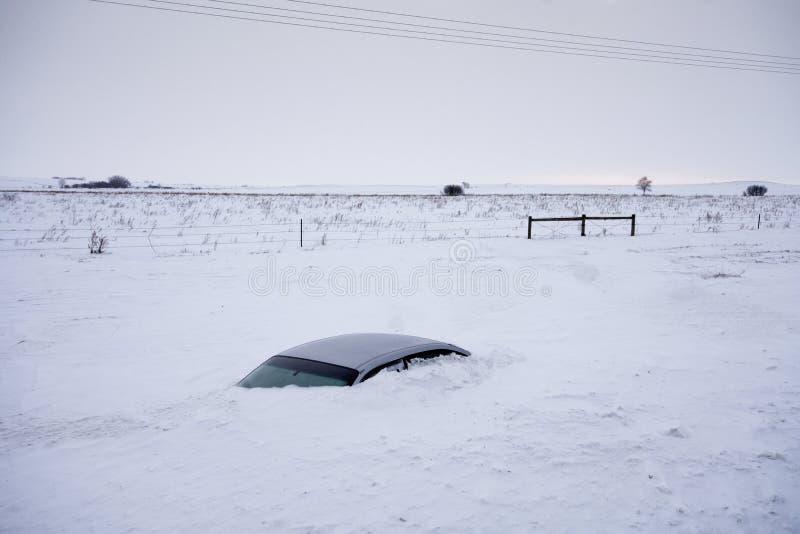 Coche enterrado a su tejado en nieve profunda no lejos del camino Dakota del Norte, los E.E.U.U. imagen de archivo