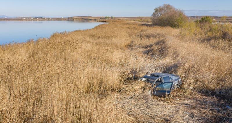 Coche estrellado en hierba seca, abandonado fotografía de archivo libre de regalías