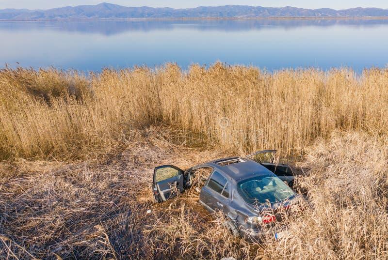 Coche estrellado en hierba seca, abandonado fotos de archivo libres de regalías