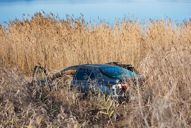 Coche estrellado en hierba seca, abandonado fotografía de archivo