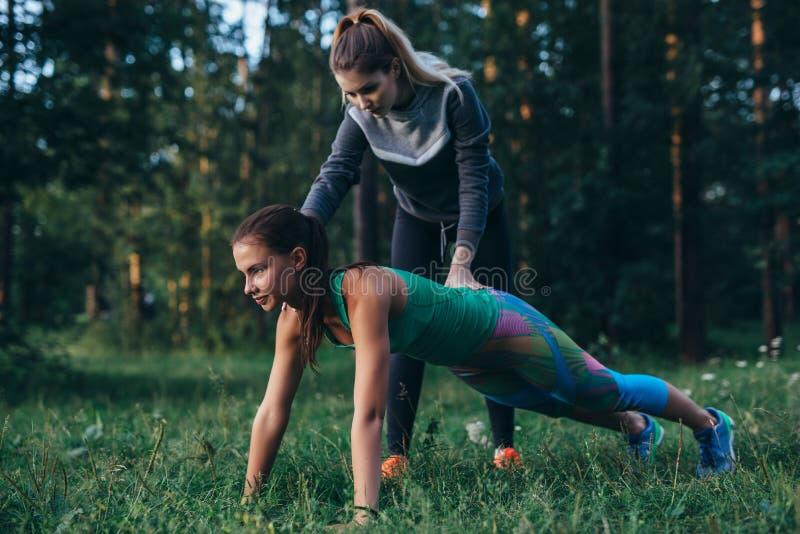 Coche femenino joven que ayuda a la deportista que hace ejercicio completo del tablón de la base en bosque imagen de archivo libre de regalías